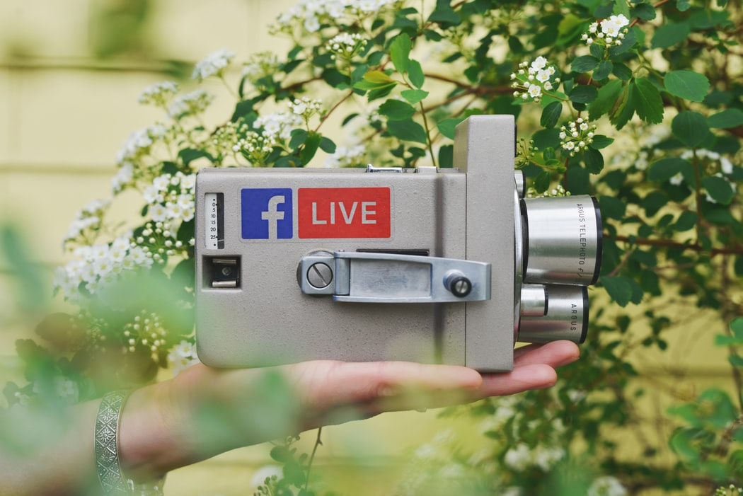 A small gray camera with the facebook live logo
