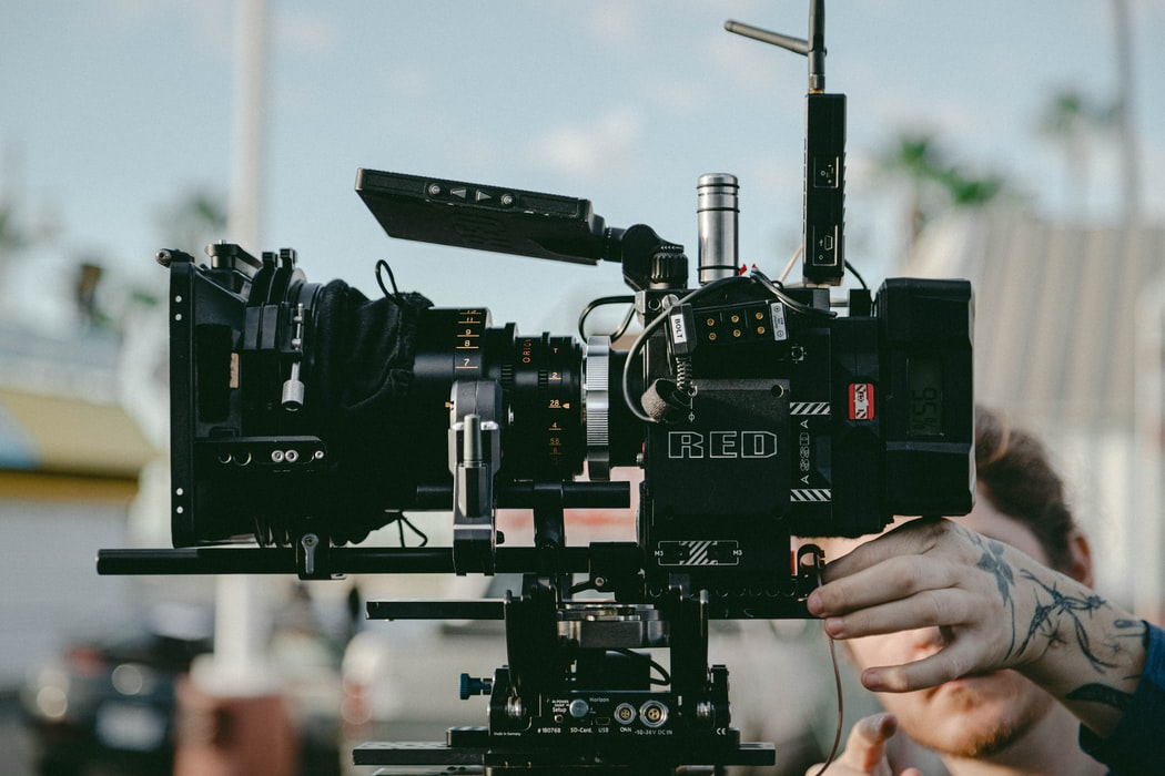 Close up image of a Red camera and a man operating it.