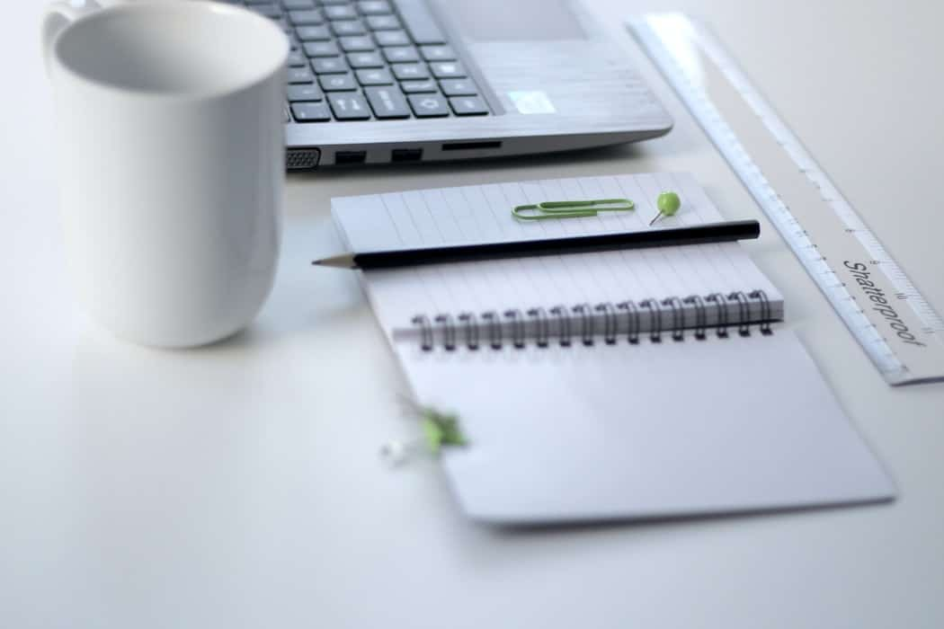 A white notebook laying open next to a white mug and laptop