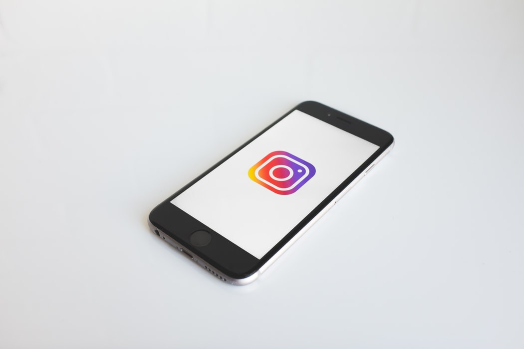 A cellphone showing the instagram logo laying on a white surface.