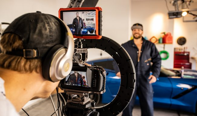 Man in a jumpsuit being filmed by a large camera with a ring light.