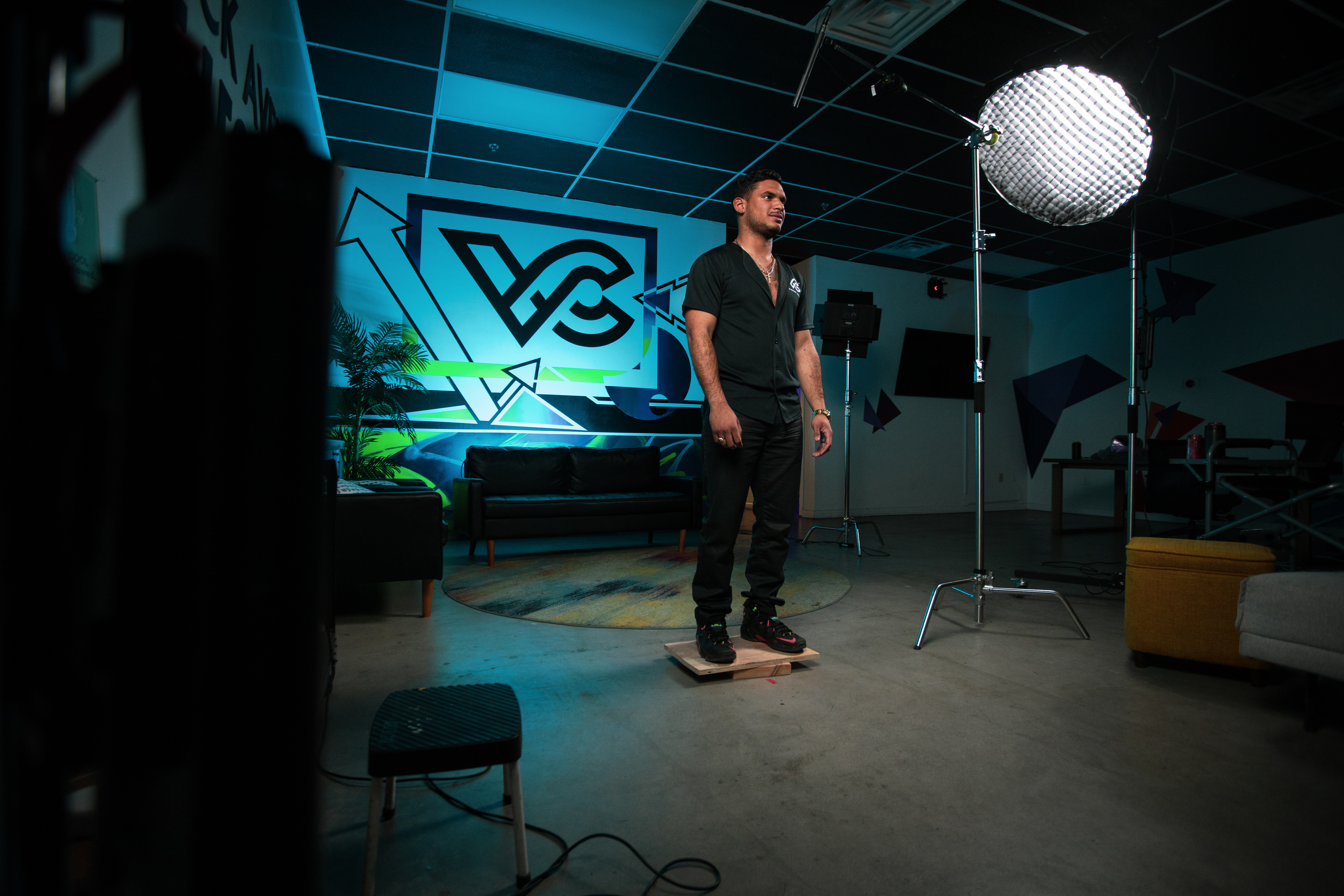 Man standing on a stage against a blue and green Viscap Media logo