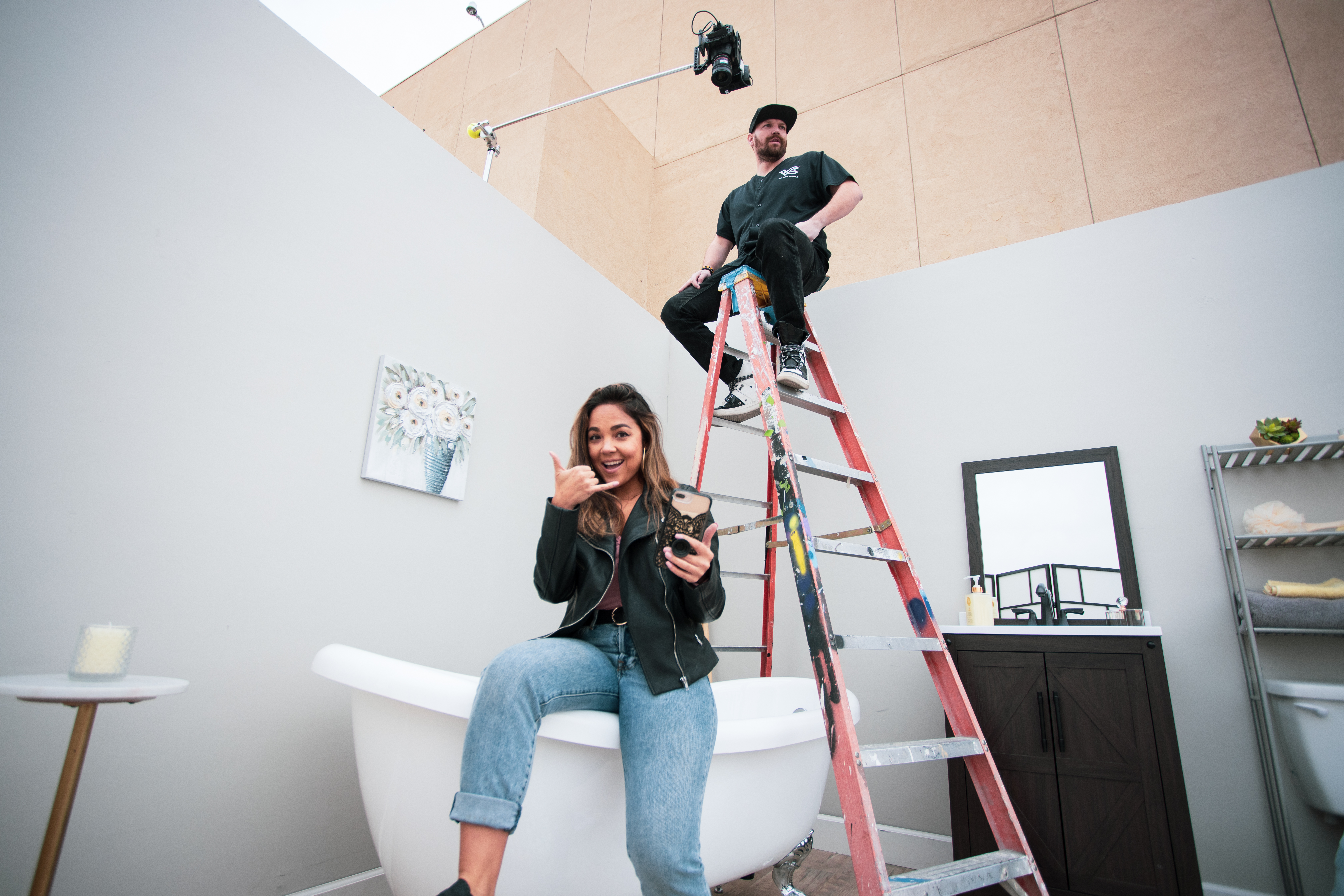 Man and woman smiling at the camera next to a bathtub and ladder.