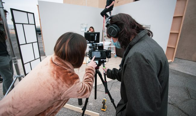 Two people looking through a camera at a movie set.