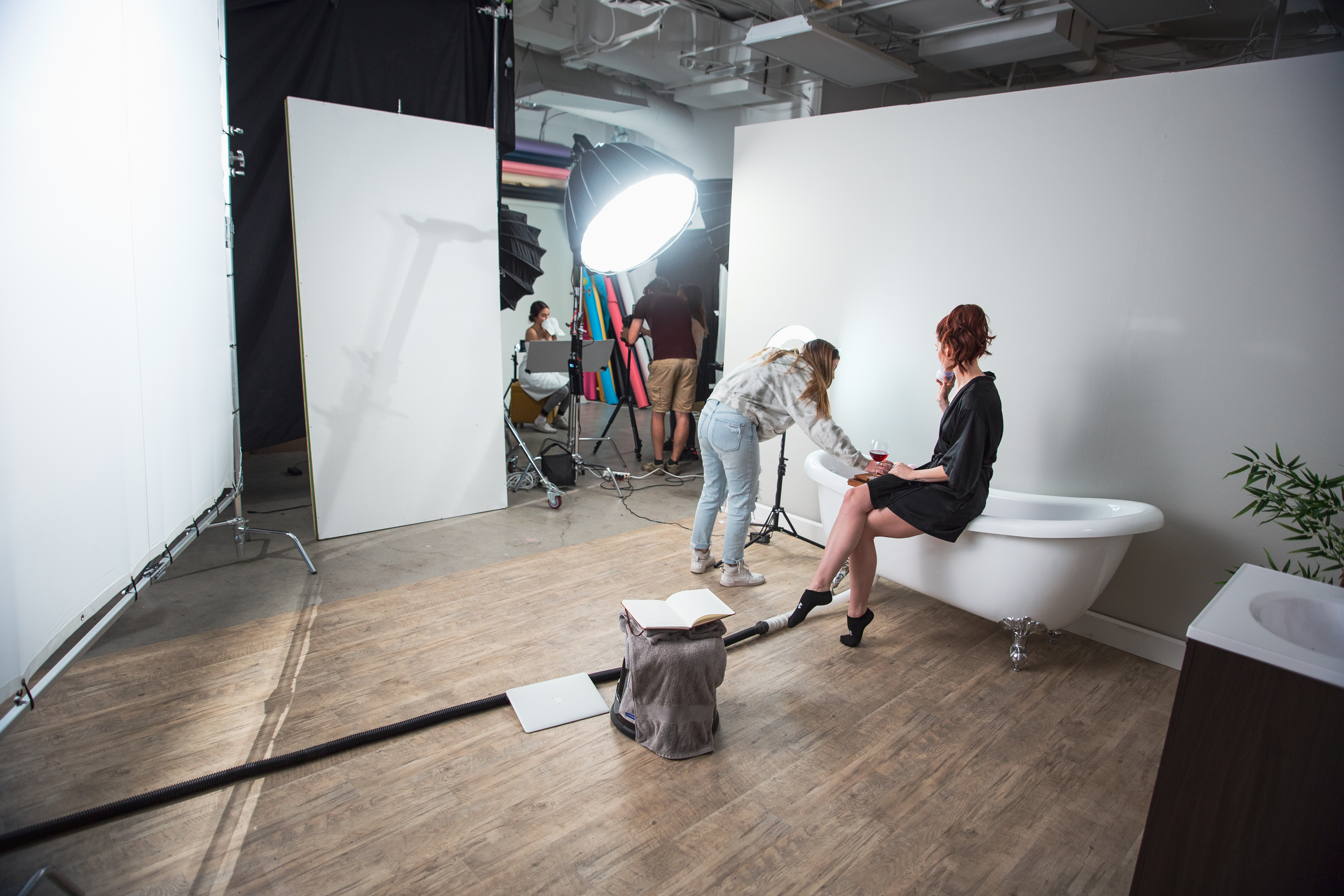 Woman sitting on the edge of a bathtub in a large room with a brown wooden floor.