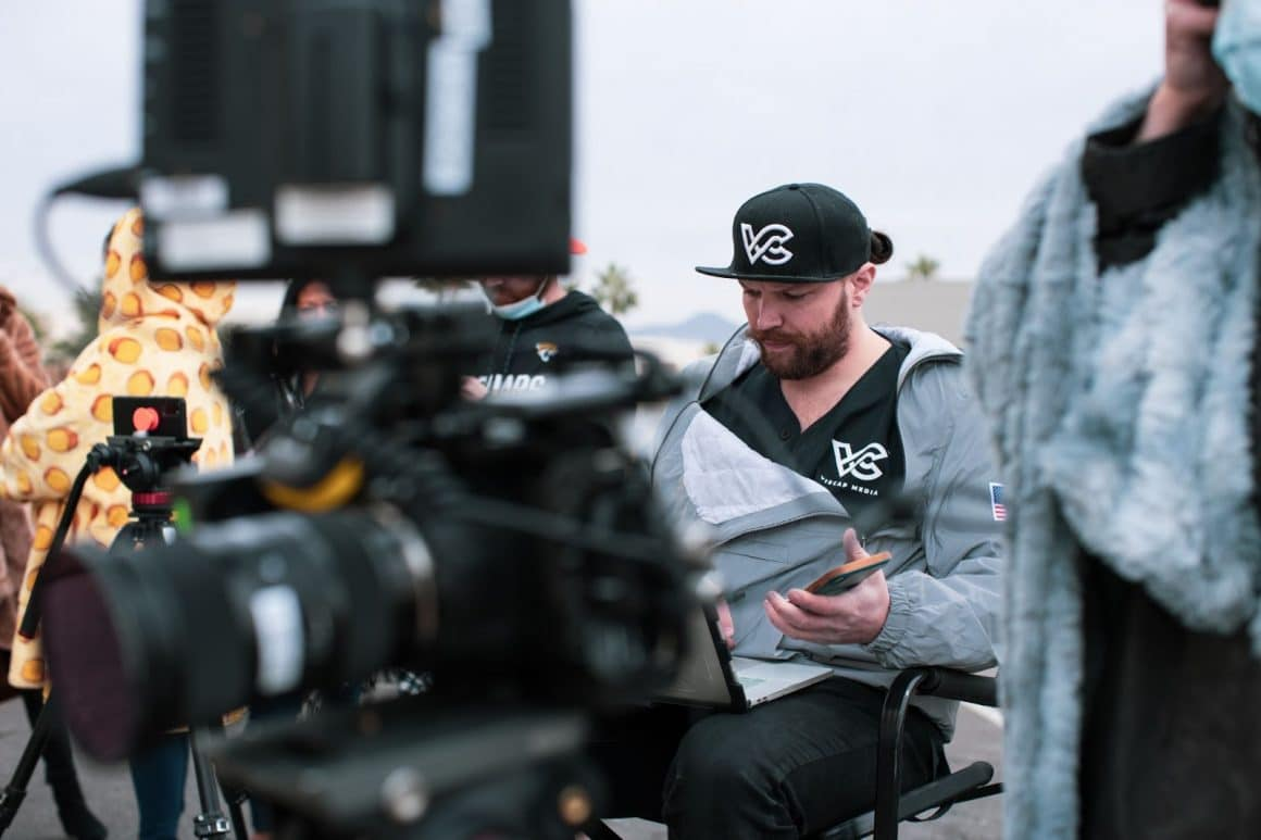 Man sitting in directors chair behind a camera reading notes from a notebook.