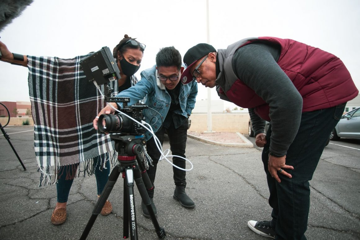group of people bending over and looking into a camera monitor on a movie set.